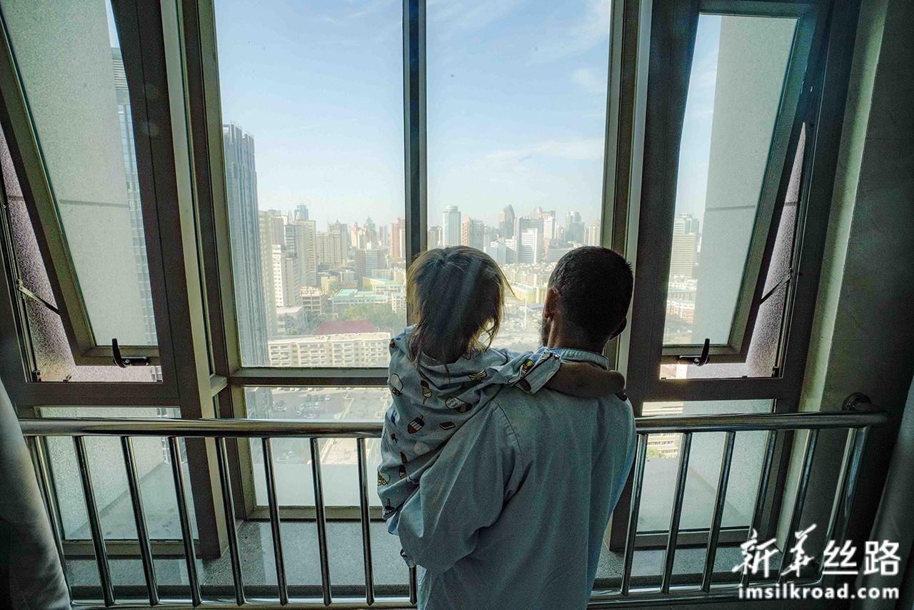 7月31日,在新疆维吾尔自治区人民医院病房里,一位来自阿富汗先心病患儿与父亲站在窗边眺望远方。新华社记者 赵戈 摄