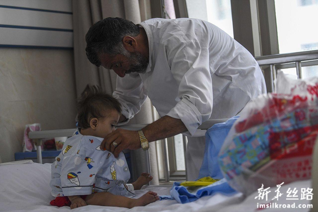 7月31日,在新疆维吾尔自治区人民医院病房里,一位来自阿富汗的先心病患儿家长给孩子换上病号服。新华社记者 赵戈 摄