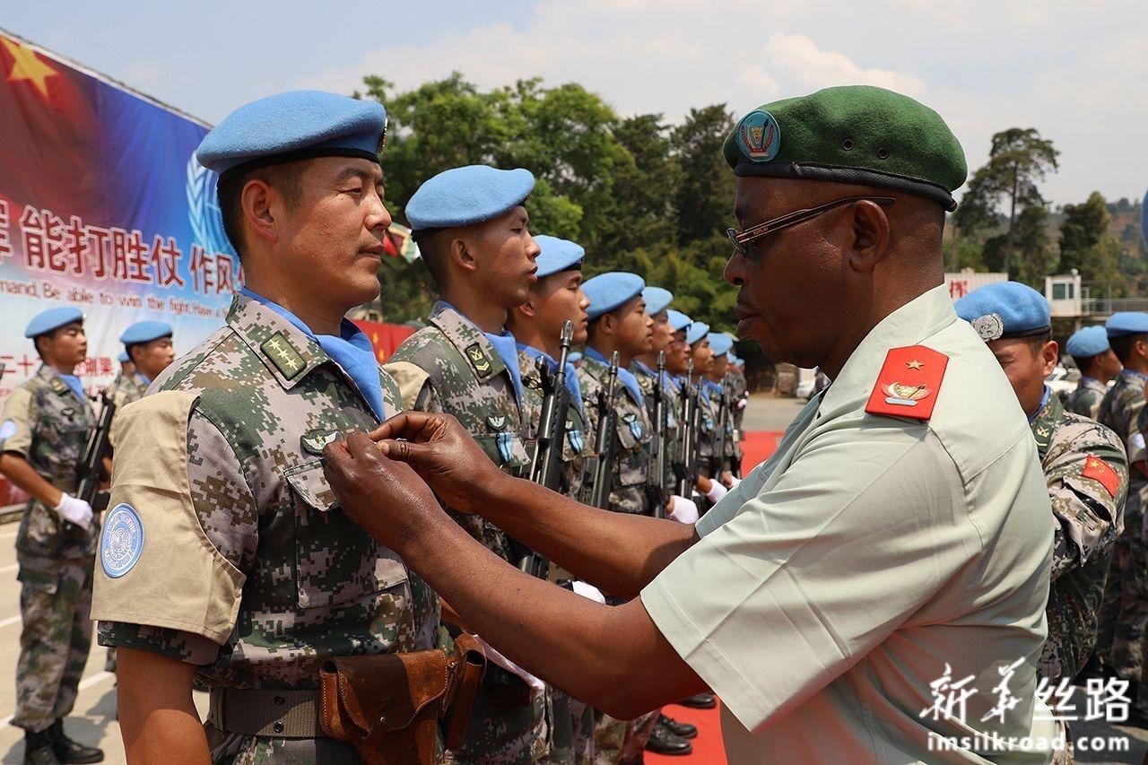"""8月8日,在刚果(金)布卡武市""""中国半岛""""营区,嘉宾代表为中国第22批赴刚果(金)维和部队官兵授勋。新华社发(李志强 摄)"""