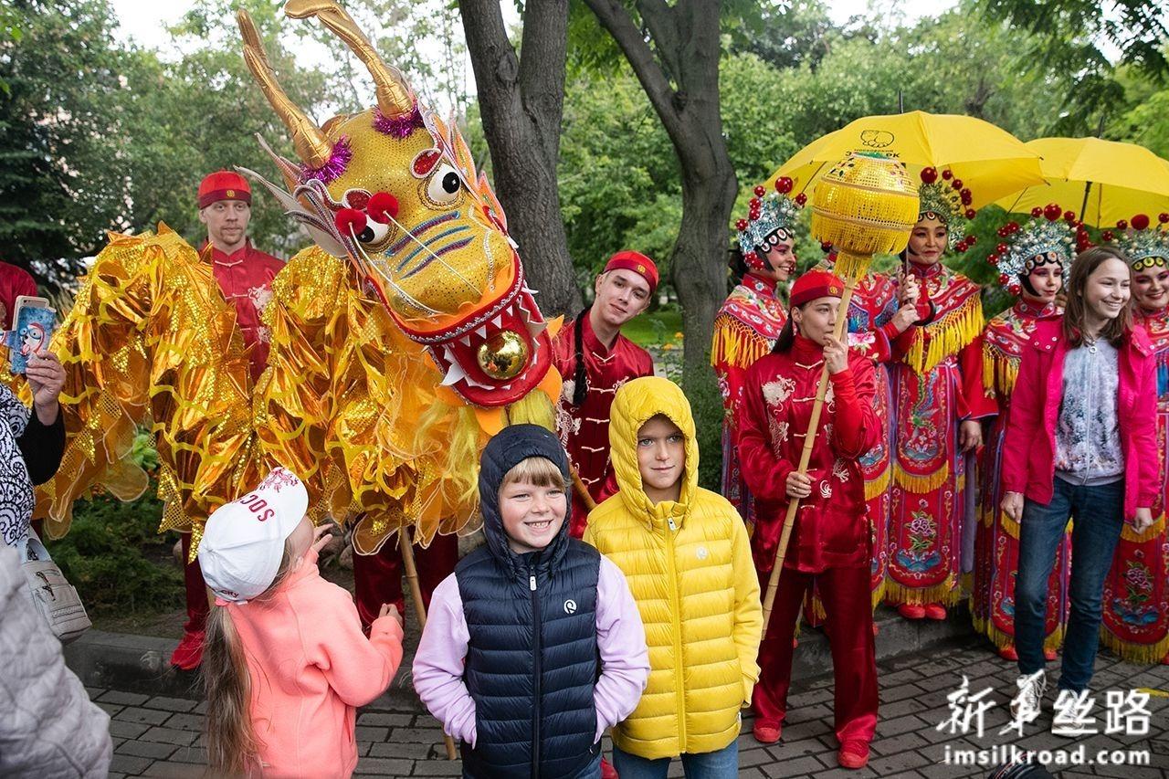 7月31日,在俄罗斯首都莫斯科,孩子们在大熊猫的生日庆祝活动上与演员合影。新华社发(叶甫盖尼·西尼岑摄)