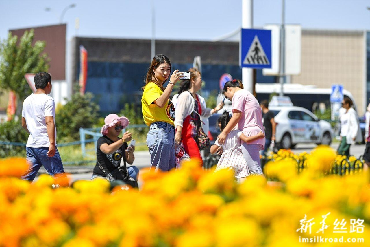 游客在中哈霍尔果斯国际边境合作中心内游玩拍照(8月11日摄)。新华社记者 胡虎虎 摄