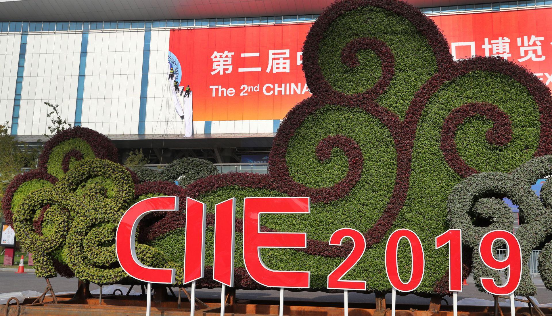10月21日,工人在国家会展中心(上海)西入口处张贴进博会标志。 新华社记者 方喆 摄