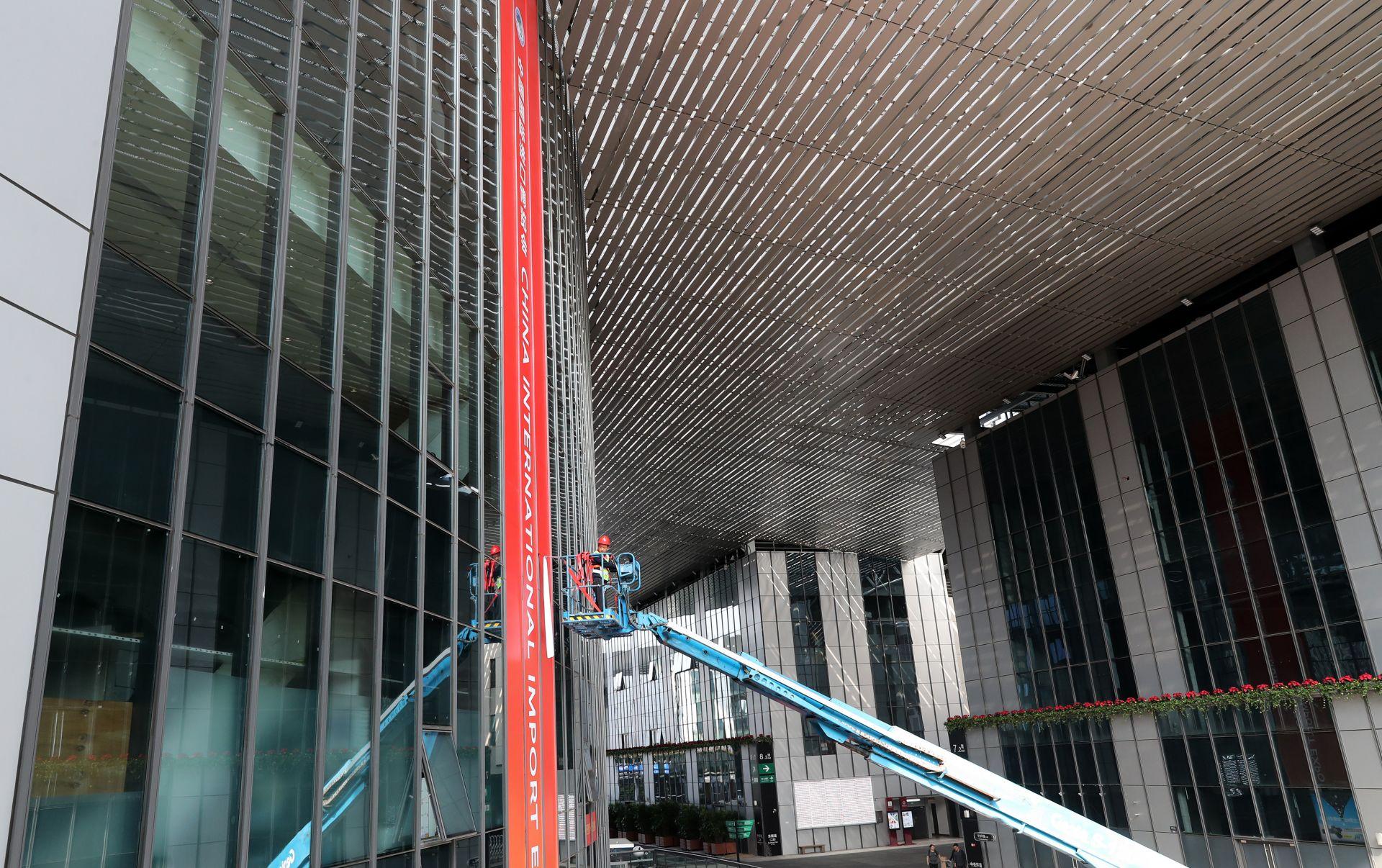 10月21日,工人乘云梯车在国家会展中心(上海)张贴进博会装饰。 新华社记者 方喆 摄