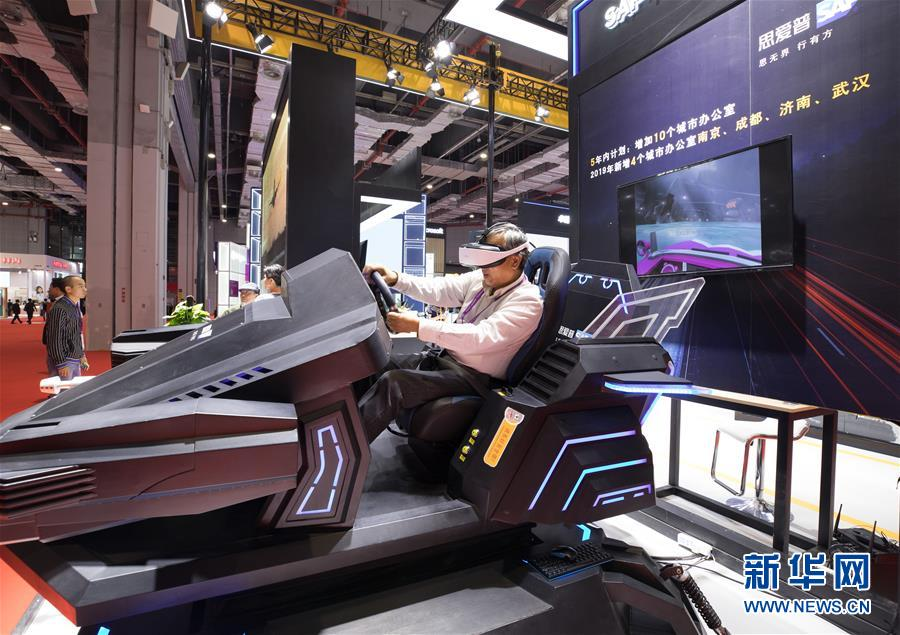 11月5日,一名参观者在第二届进博会科技生活展区体验虚拟现实赛车。 当日,第二届中国国际进口博览会在上海国家会展中心开幕。 新华社记者 金立旺 摄