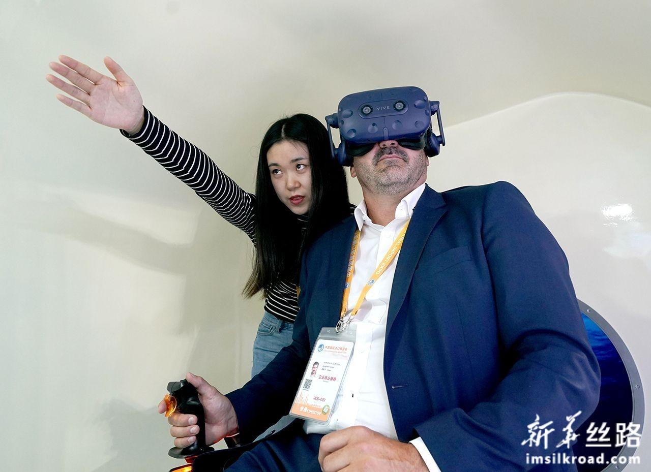 """11月5日,一位来自西班牙的参展商(右)在中国馆""""深海勇士""""号载人潜水器模拟舱中体验深潜。新华社记者 陈建力 摄"""