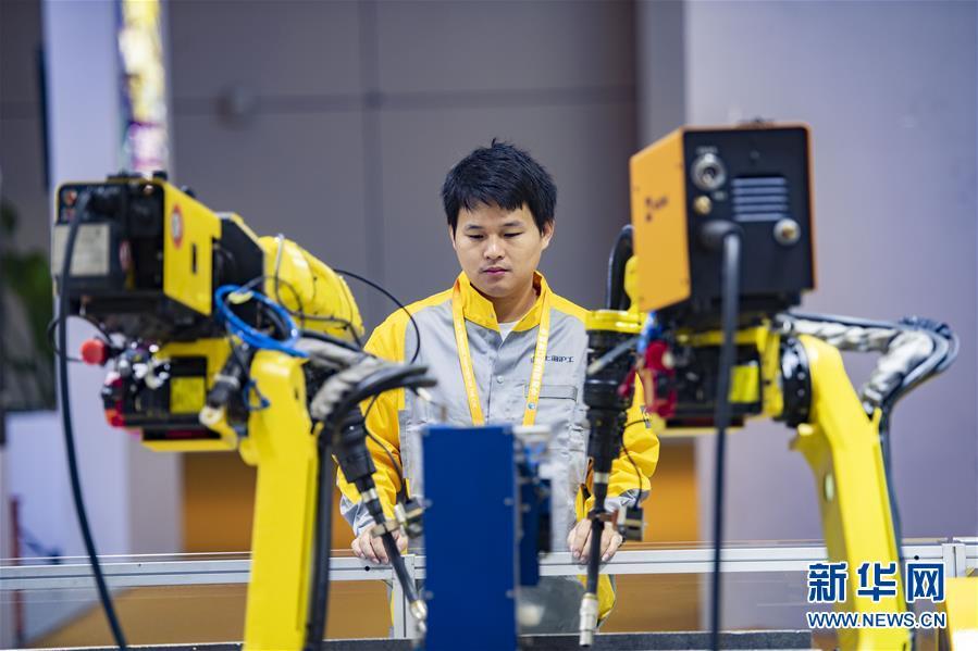 11月5日,在第二届进博会装备展区,工作人员在沪工国际(香港)有限公司展台前查看点焊机器人设备运行情况。 当日,第二届中国国际进口博览会在上海国家会展中心开幕。 新华社记者 普布扎西 摄