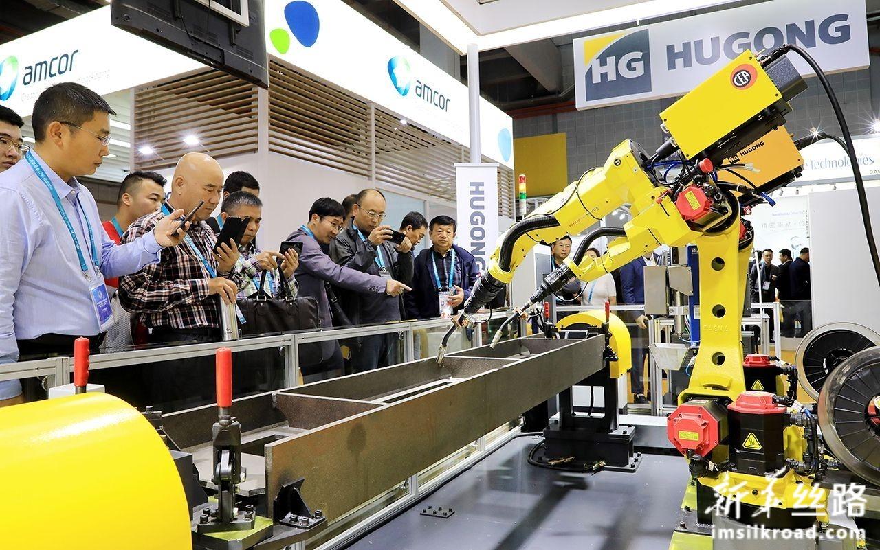 11月6日,在进博会装备展区,一组正在进行作业演示的焊接机器人吸引了参观者的目光。新华社记者 方喆 摄