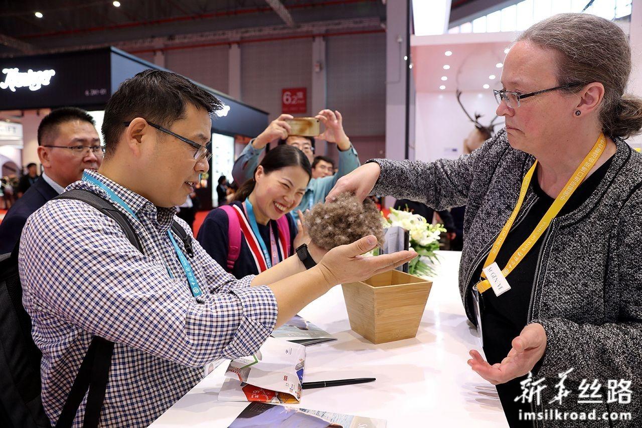 11月6日,在品质生活展区一家澳大利亚床上用品展台,参观者体验野生灰雁绒的手感。新华社记者 刘颖 摄