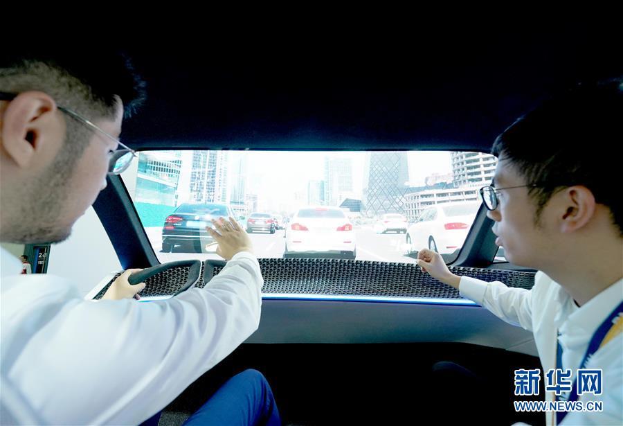 """11月5日,技术工程人员(右)在第二届进博会汽车展区宝马展台""""超界面""""沉浸式数字体验仓内向参观者介绍。 当日,第二届中国国际进口博览会在上海国家会展中心开幕。 新华社记者 陈建力 摄"""