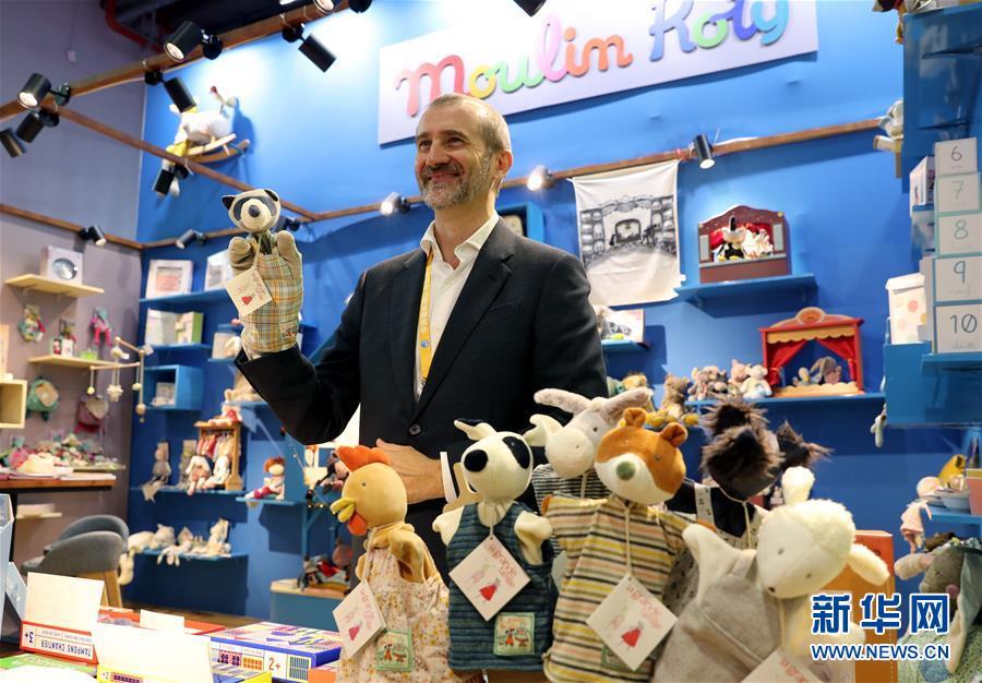 11月5日,在第二届进博会品质生活展区,来自法国的玩具品牌展商手持儿童手偶玩具。 当日,第二届中国国际进口博览会在上海国家会展中心开幕。 新华社记者 刘颖 摄