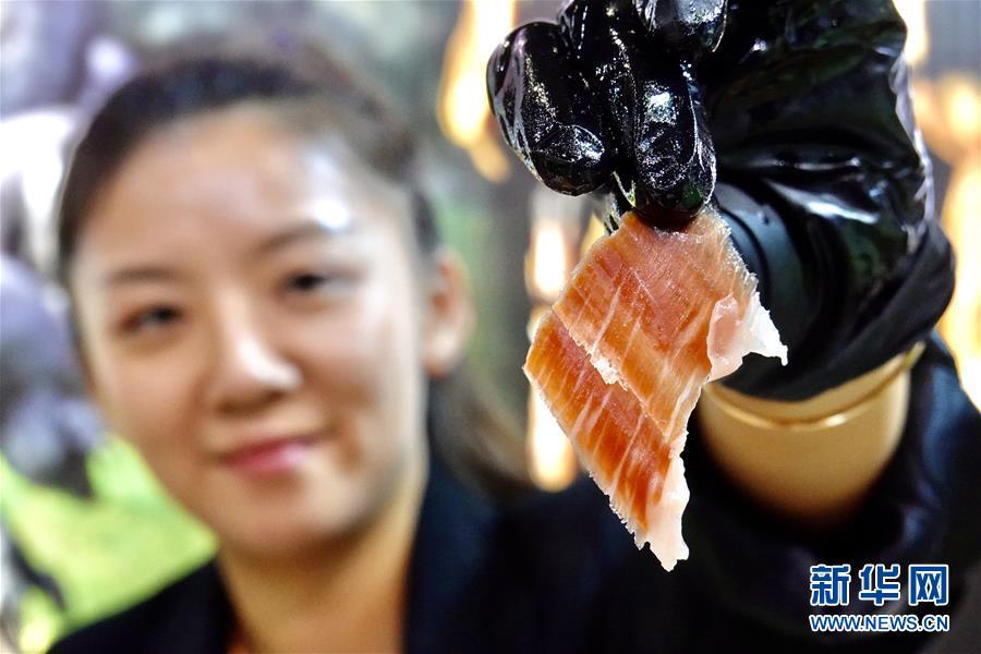 11月5日,在第二届进博会食品及农产品展区,工作人员展示西班牙橡果火腿。 当日,第二届中国国际进口博览会在上海国家会展中心开幕。 新华社记者 才扬 摄