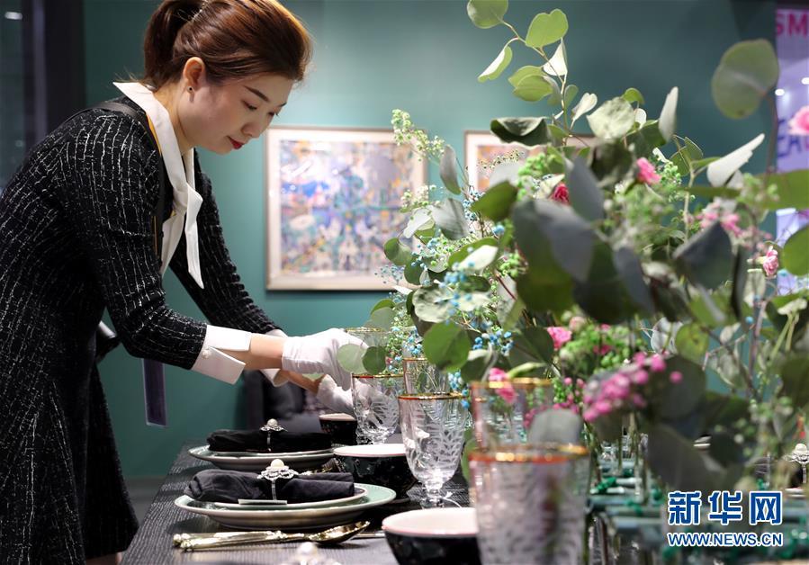 11月5日,在第二届进博会品质生活展区,工作人员在一家丹麦家居产品的展台前忙碌。 当日,第二届中国国际进口博览会在上海国家会展中心开幕。 新华社记者 刘颖 摄