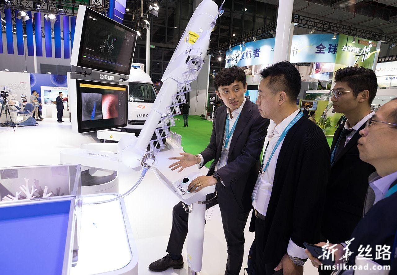 11月7日,在第二届进博会医疗器械及医药保健展区,参观者了解用于肺癌早期诊断和治疗的机械臂辅助导航支气管镜系统。新华社记者 金立旺 摄
