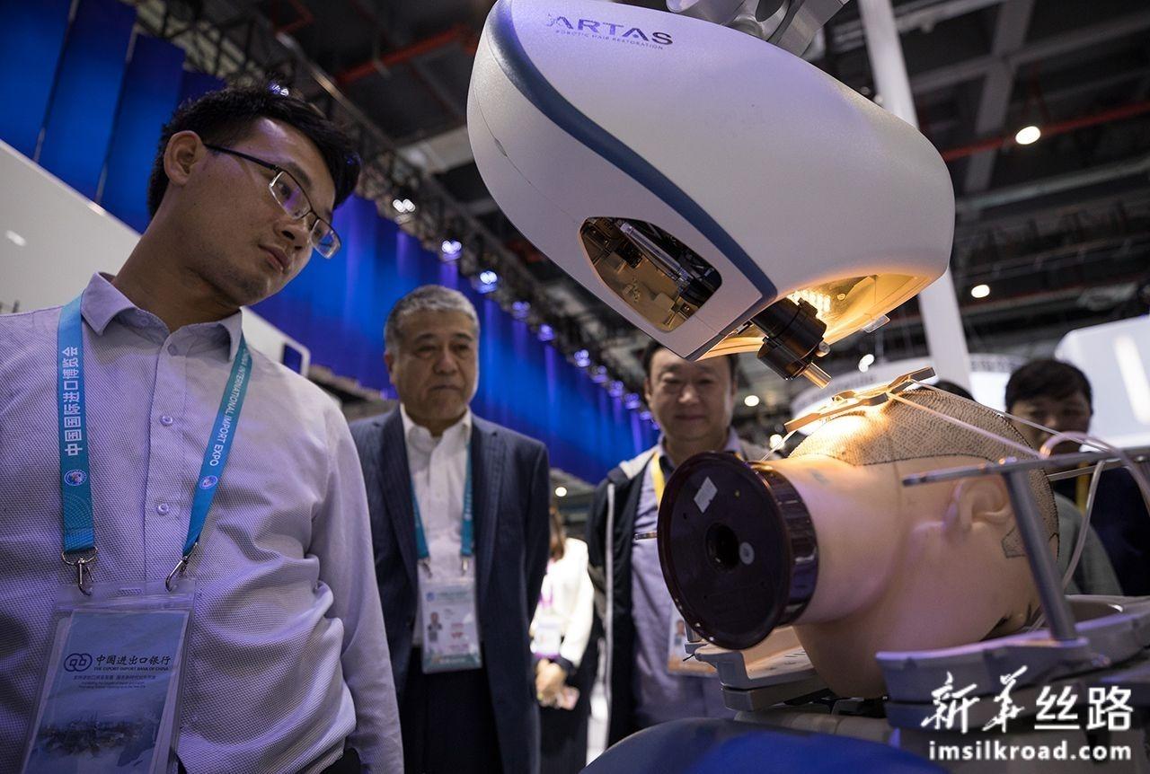 11月7日,在第二届进博会医疗器械及医药保健展区,参观者了解一款可以实现人工植发的机器人。新华社记者 金立旺 摄