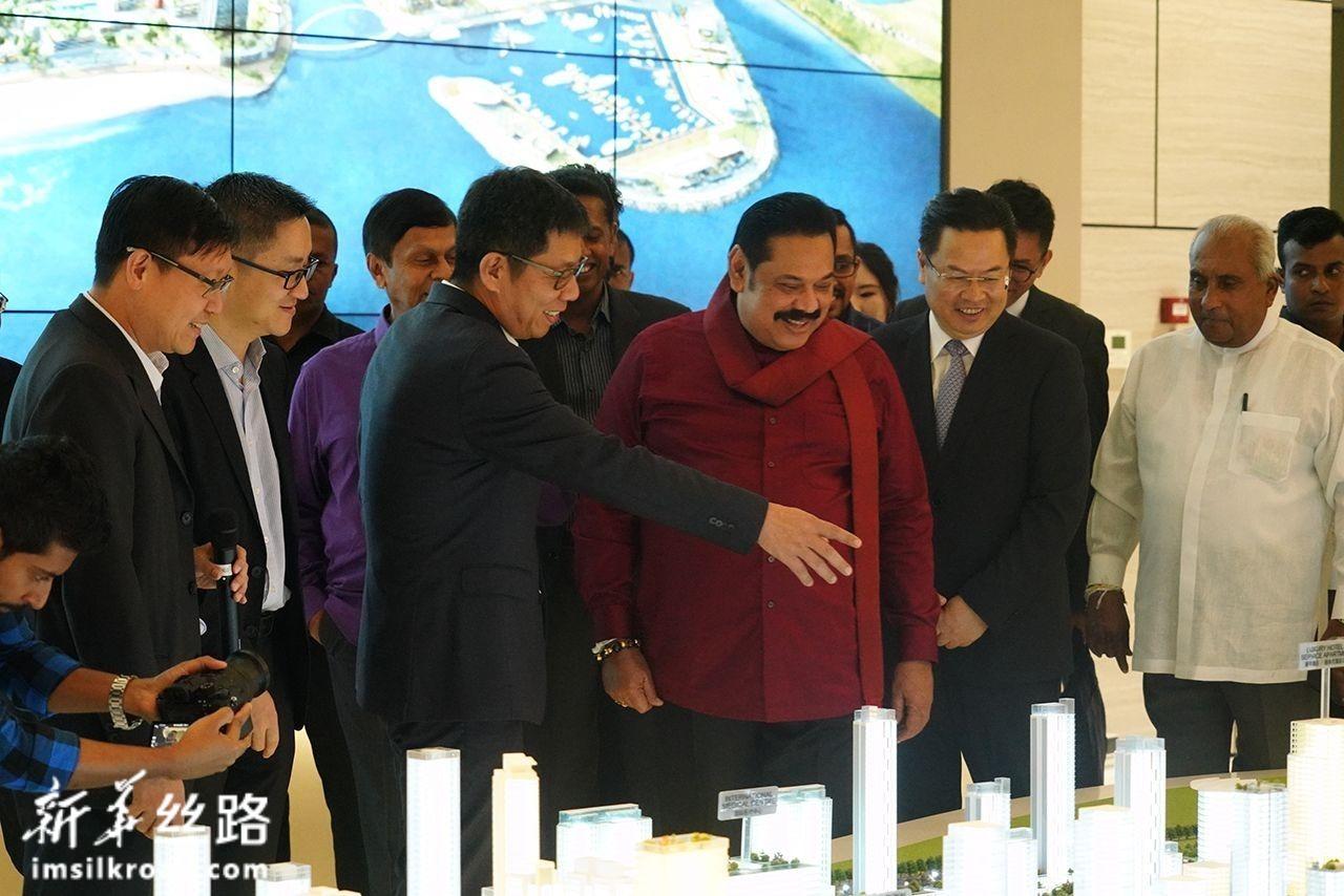 12月7日,在斯里兰科伦坡,斯里兰卡总理马欣达·拉贾帕克萨(前排中)在港口城项目展厅沙盘前听取介绍。新华社记者 唐璐 摄