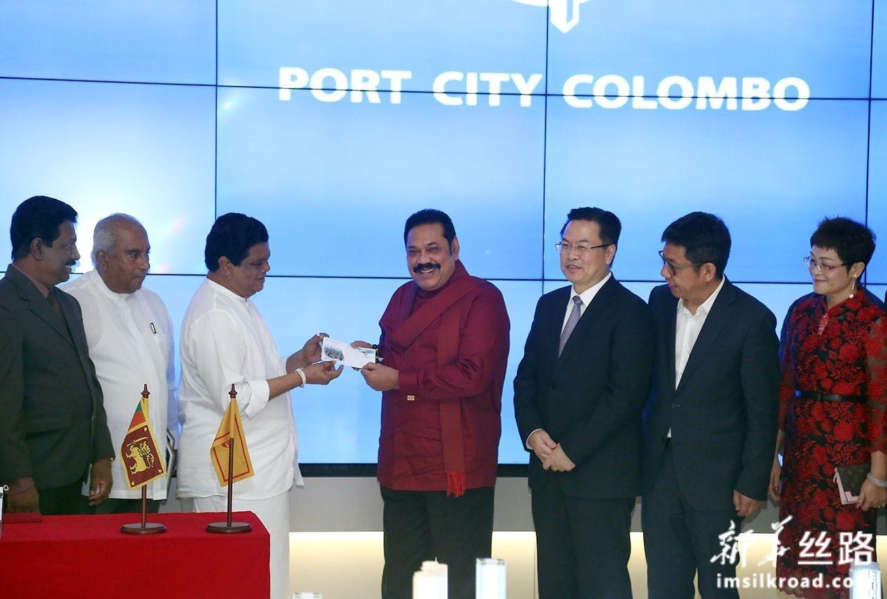 12月7日,在斯里兰卡科伦坡,斯总理马欣达·拉贾帕克萨(右四)见证斯里兰卡邮政局为港口城设计的邮票和首日封发行。新华社发(阿吉特·佩雷亚摄)