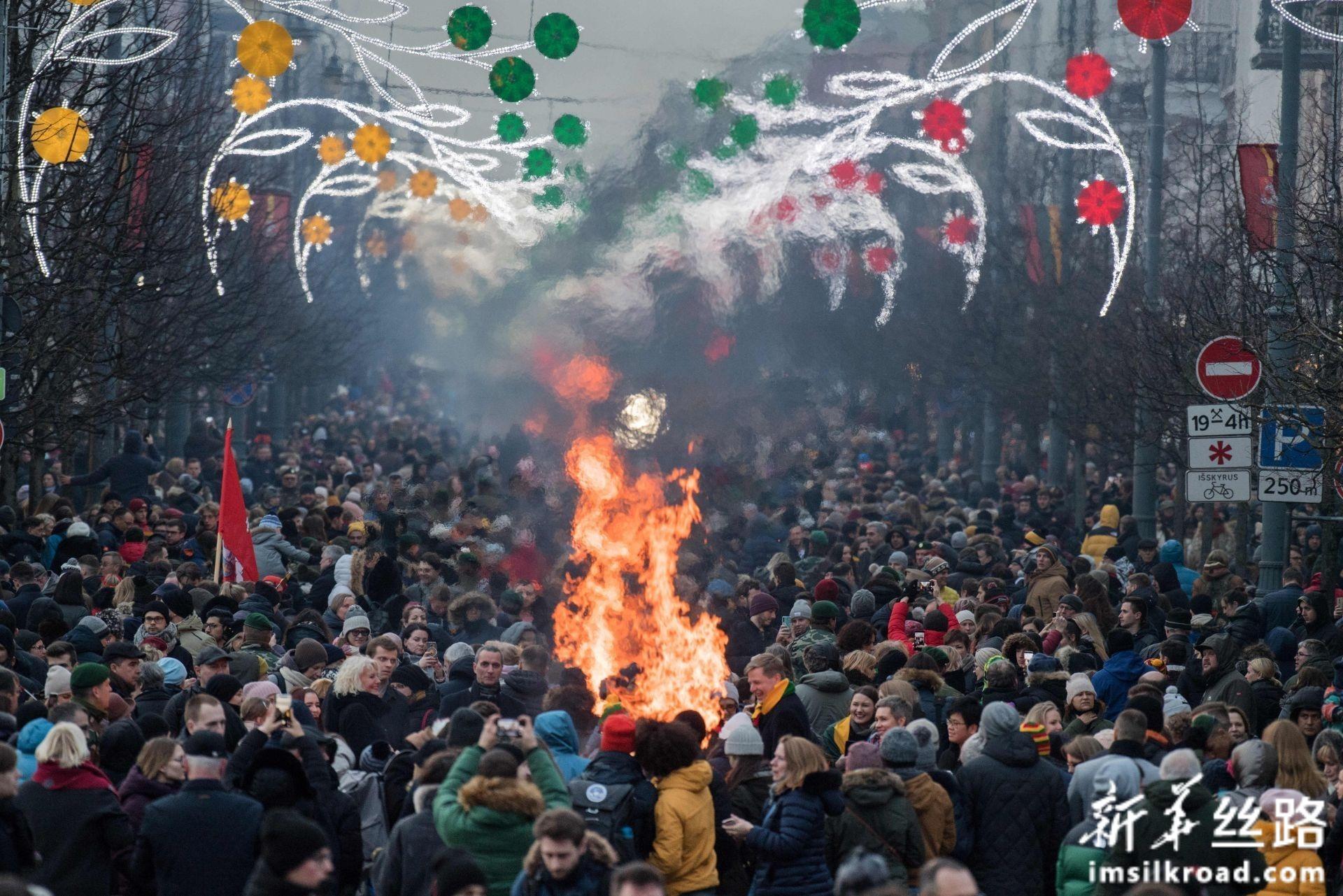 2月16日,在立陶宛首都维尔纽斯,民众围在篝火旁庆祝独立日。新华社发(阿尔弗雷达斯·普里亚迪斯摄)