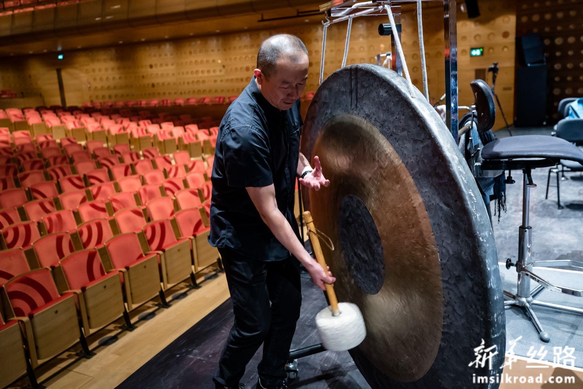 2月14日,在比利时安特卫普,谭盾在排练现场展示武汉铜锣。新华社记者 张铖 摄