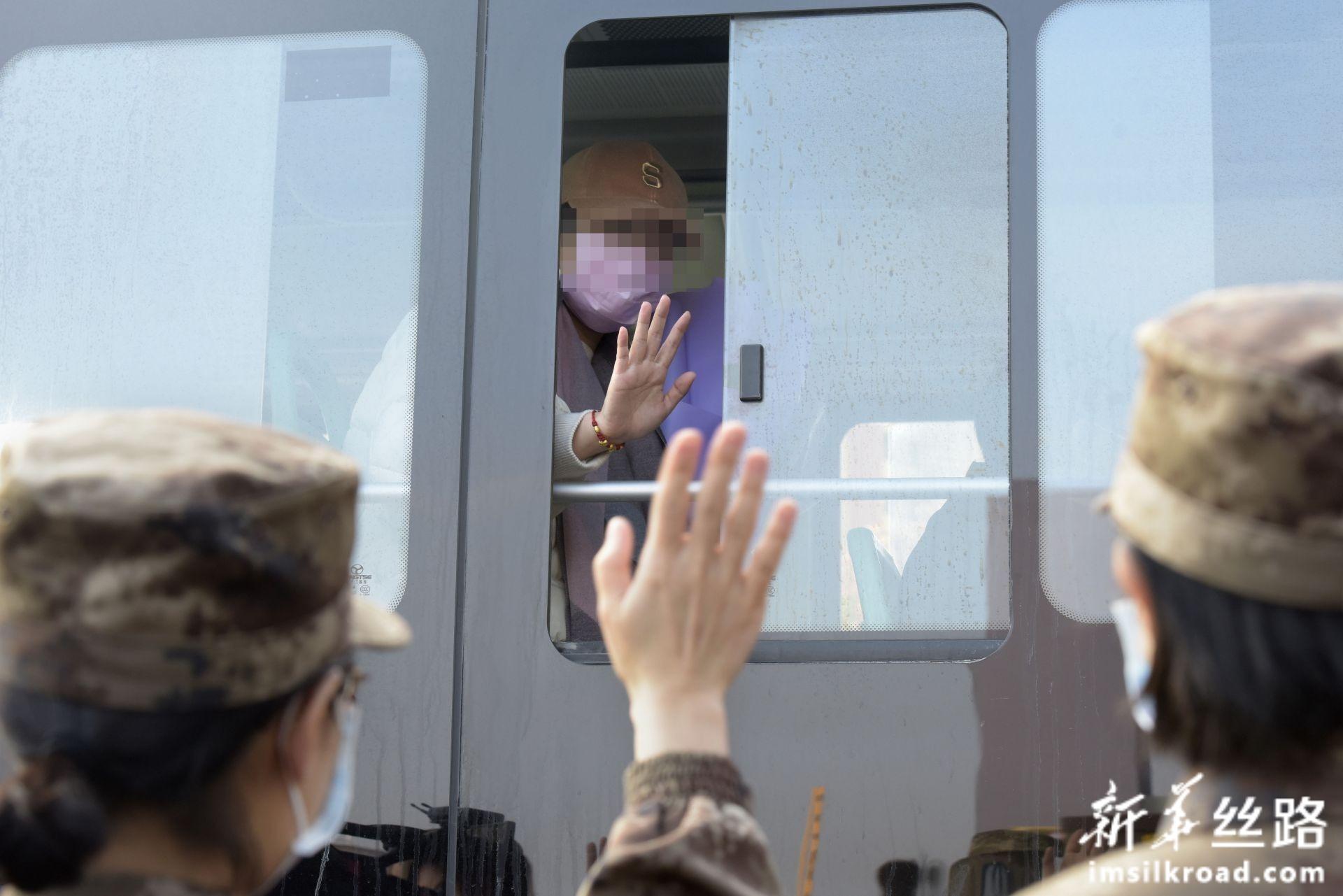 2月13日,在武汉火神山医院,治愈患者与医疗队队员挥手道别。新华社发(范显海 摄)