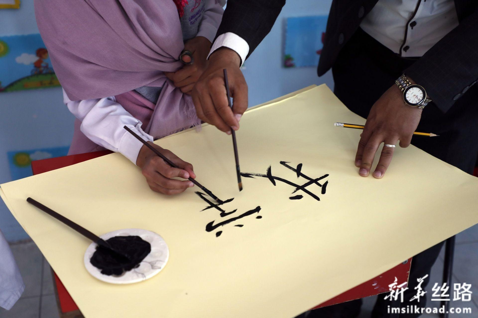 2月10日,在也门首都萨那,汉语老师穆罕默德·安西教学生写汉字。新华社发(穆罕默德摄)