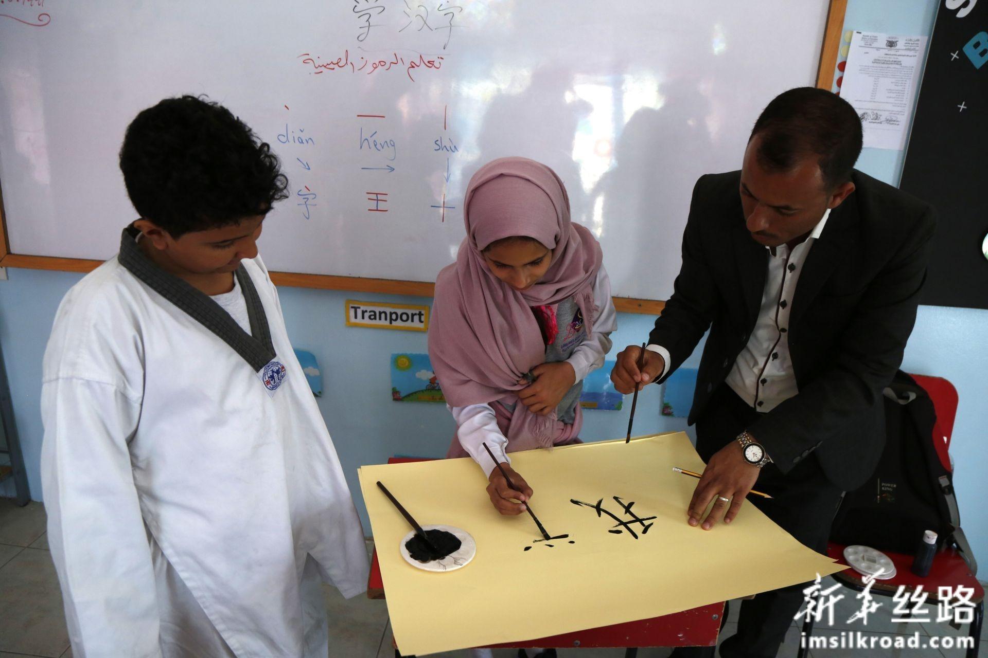 2月10日,在也门首都萨那,汉语老师穆罕默德·安西(右一)教学生写汉字。新华社发(穆罕默德摄)