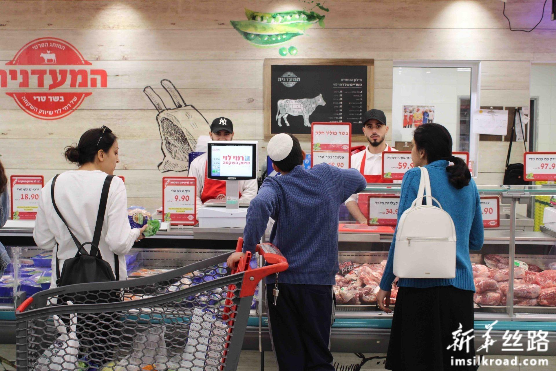 """2月13日,顾客在耶路撒冷附近的阿塔罗特一家超市购物,这家企业被列入联合国人权高专办公布的""""黑名单""""。新华社记者 尚昊 摄"""