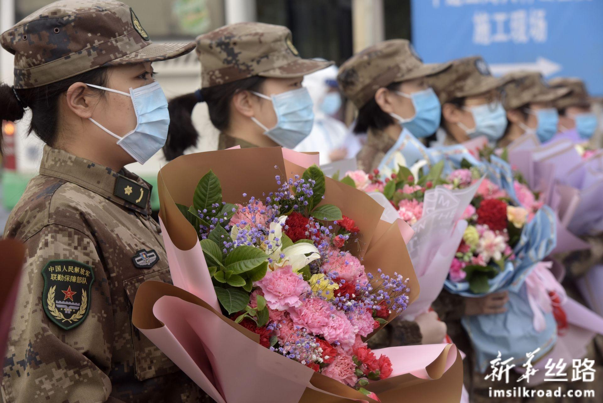 2月13日,在武汉火神山医院,医疗队队员手捧鲜花等候治愈患者出院。新华社发(范显海 摄)