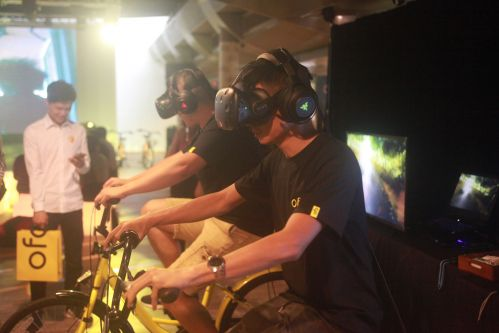 两名ofo工作人员在演示用虚拟现实技术感受骑行乐趣