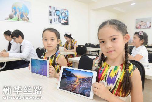 6月21日,在乌兹别克斯坦塔什干第59中学,两名乌兹别克斯坦女学生在华为公司捐赠的智慧教室内展示教学设备 记者沙达提摄
