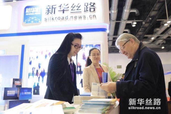 参加外洽会的各国嘉宾翻看新华丝路产品介绍。新华社记者 周懿摄