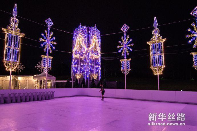 """图1 游客经过通往""""圣诞仙境""""主场地的圣诞灯饰走廊(新华社发 符传威摄)"""