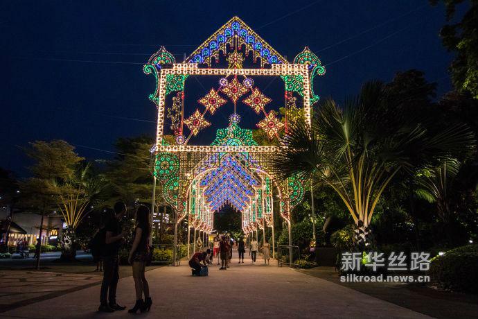 图4 游客们经过装设在滨海湾花园擎天树丛下的巨型圣诞灯饰(新华社发 符传威摄)