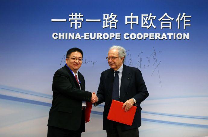 中国经济信息社副总裁匡乐成(左)与意大利克拉斯集团总裁Paolo Panerai(右)交换合作备忘录文本