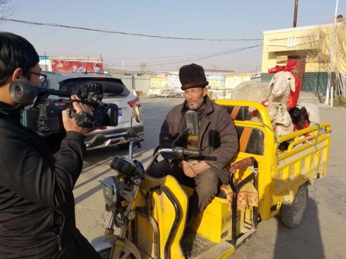 图三为贫困户阿迪力·达依木拿到羊后接受记者采访的场面