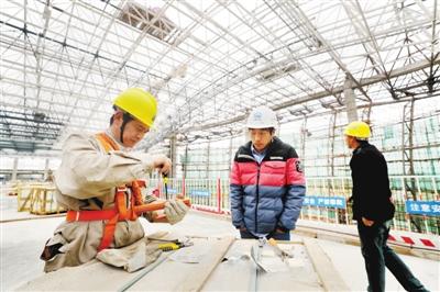 高铁湛江西客站站房里,工人在抓紧施工。