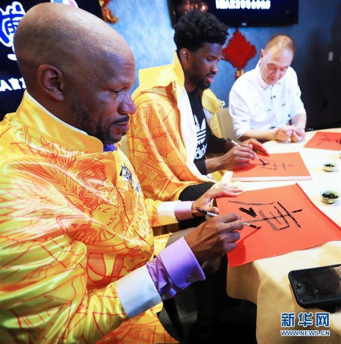 2月15日,传奇球星罗恩·哈珀(左)和NBA费城76人队球星恩比德(中)练习中国书法。新华社记者李颖
