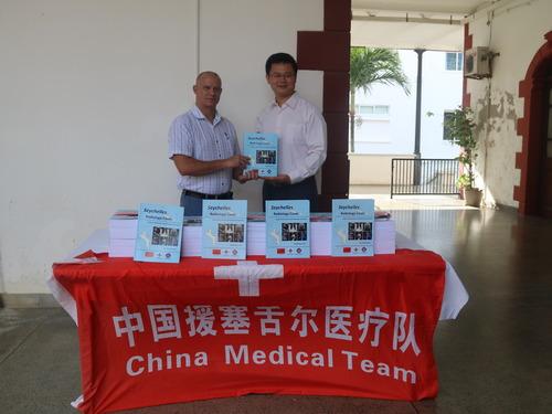 7月17日,在位于塞舌尔蒙弗勒里的塞舌尔医院,中国第16批援塞舌尔医疗队队员孙占国(右)将《塞舌尔放