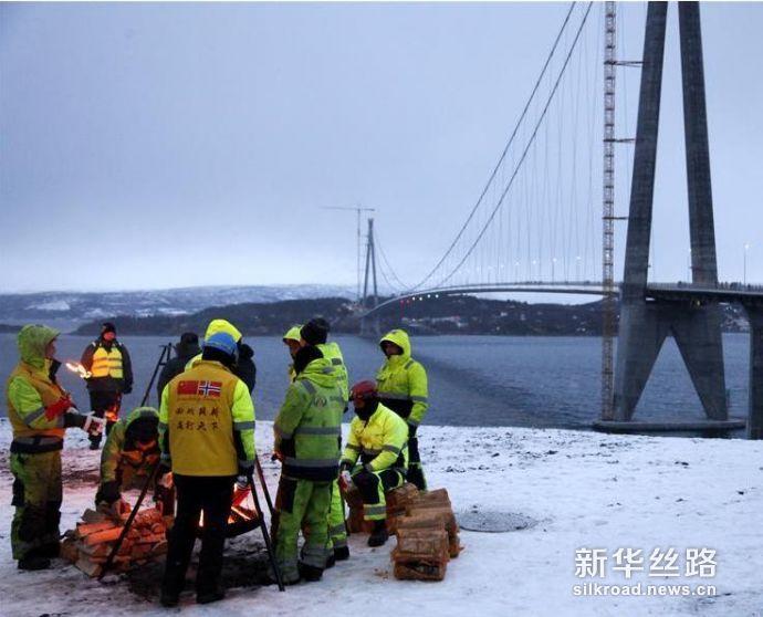 图为12月9日,中国工人在挪威哈罗格兰德大桥旁烤火取暖。 新华社记者梁有昶摄