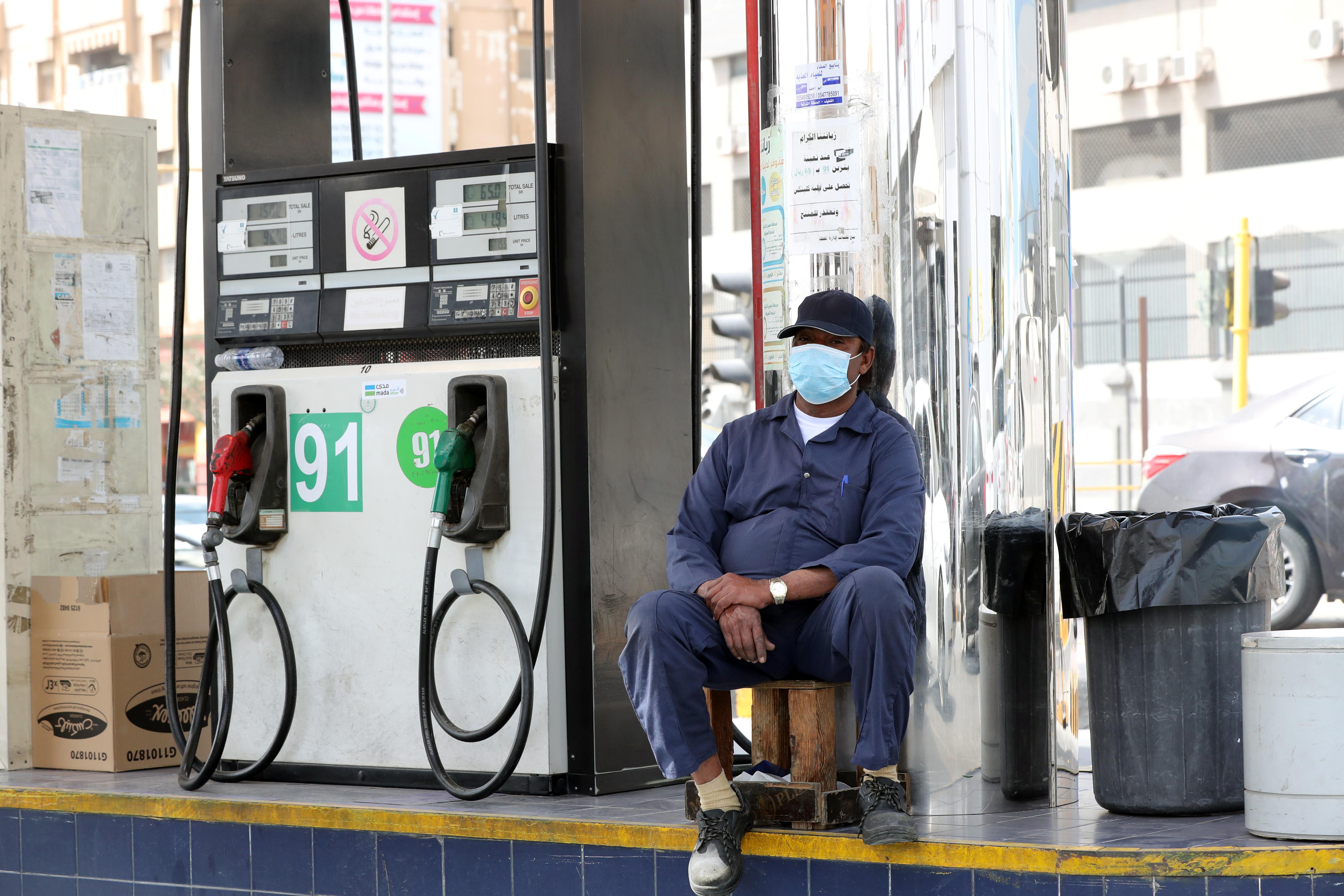 3月9日,在沙特阿拉伯城市盖提夫,加油站工作人员戴着口罩等候顾客。.JPG