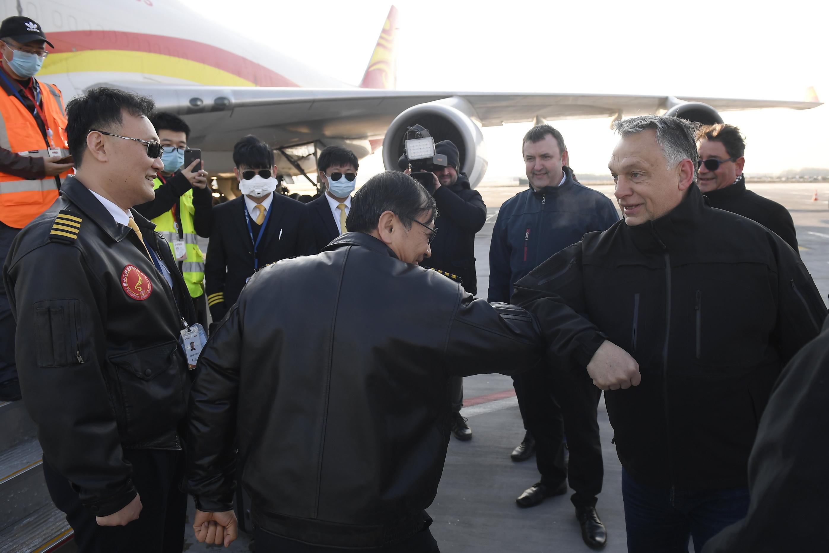 新华社照片,布达佩斯,2020年3月25日 3月24日,在匈牙利布达佩斯李斯特国际机场,匈总理欧尔班(右一)与中方机组人员相互致意。新华社发(陶马什·科瓦奇 摄)