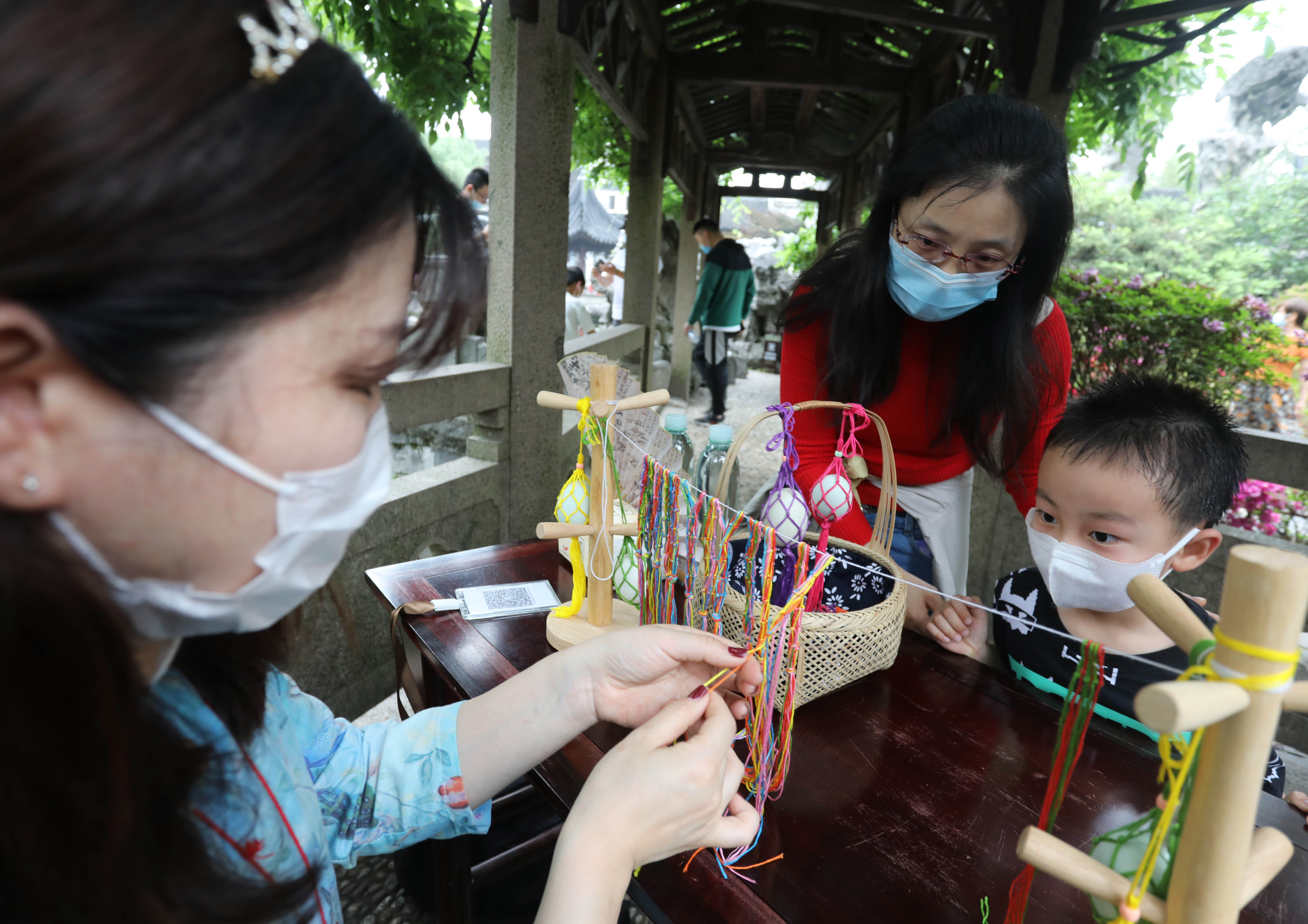 新华社照片,苏州(江苏),2020年5月5日 5月5日,游客在苏州古典园林狮子林观看工作人员编制蛋网。 新华社发(杭兴微摄)