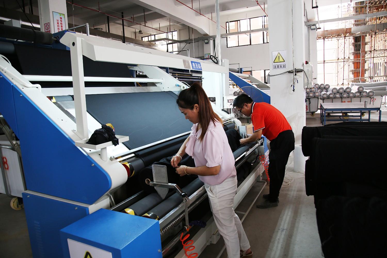 中国(贵港)纺织服装时尚新区入园企业工人在调试设备(莫新雄摄).jpg